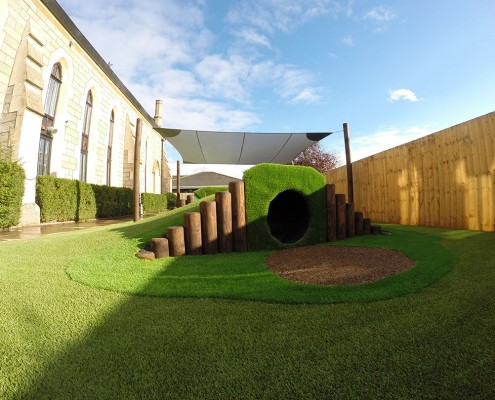 A picture of a play area with artificial grass installed by All Weather Play, a Turf King company. Turf King is a family run business dedicated to excellence in artificial grass